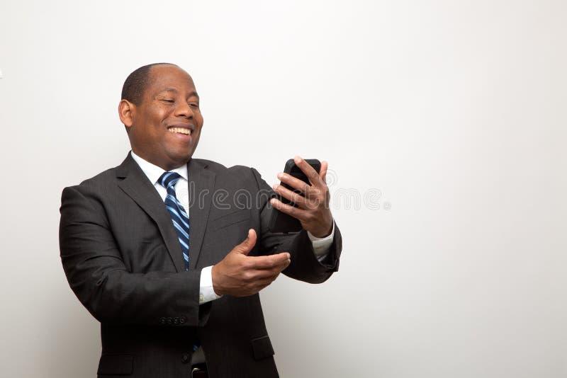 Homem de negócio afro-americano feliz que tem o divertimento com telefone celular fotografia de stock
