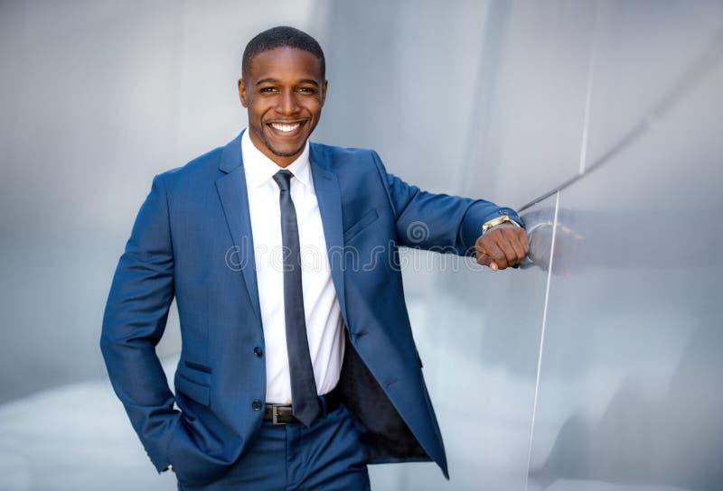 Homem de negócio afro-americano moderno à moda, retrato de sorriso considerável ao lado da construção financeira fotos de stock royalty free