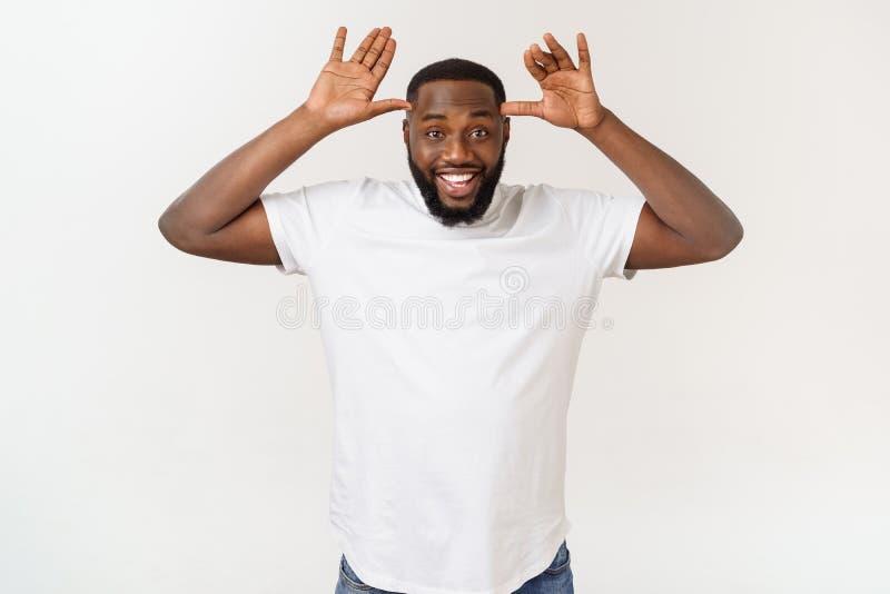 Homem de negócio afro-americano novo com sorriso e riso com mão na cara que cobre os olhos para a surpresa cortina imagem de stock