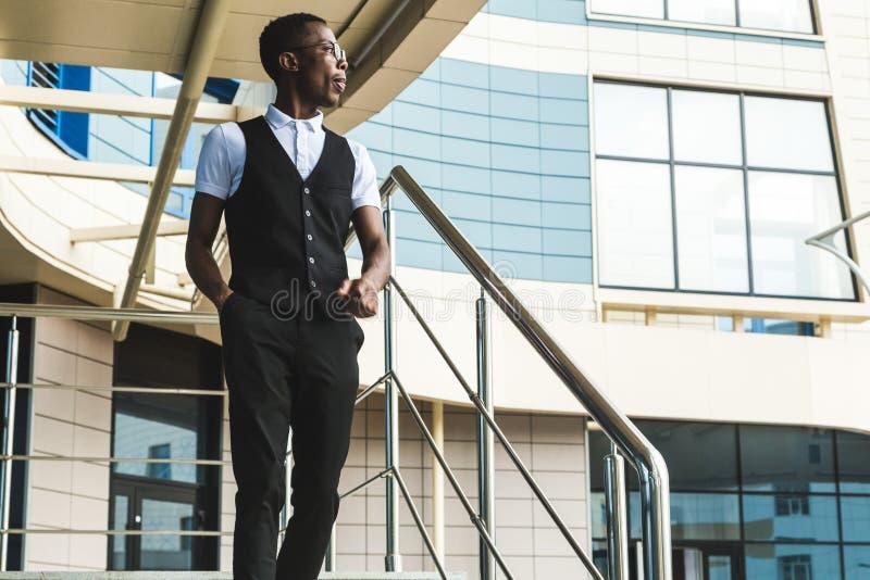 Homem de negócio afro-americano novo no terno e monóculos que falam no telefone no fundo do centro de negócios imagens de stock royalty free