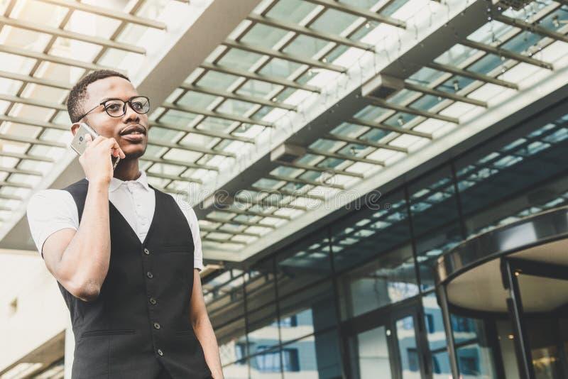 Homem de negócio afro-americano novo no terno e monóculos que falam no telefone no fundo do centro de negócios imagens de stock
