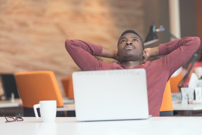 Homem de negócio afro-americano novo que toma uma ruptura em sua mesa fotografia de stock