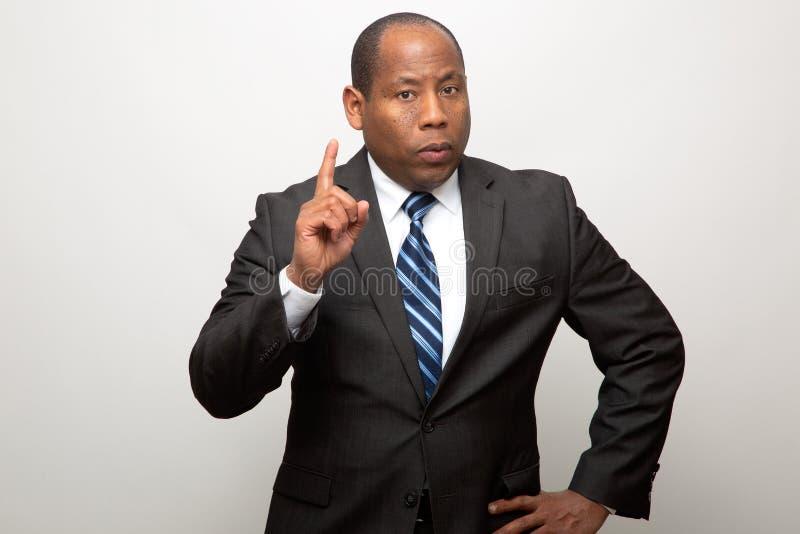 Homem de negócio afro-americano que aponta com o dedo no sinal do conselho e da advertência imagem de stock royalty free