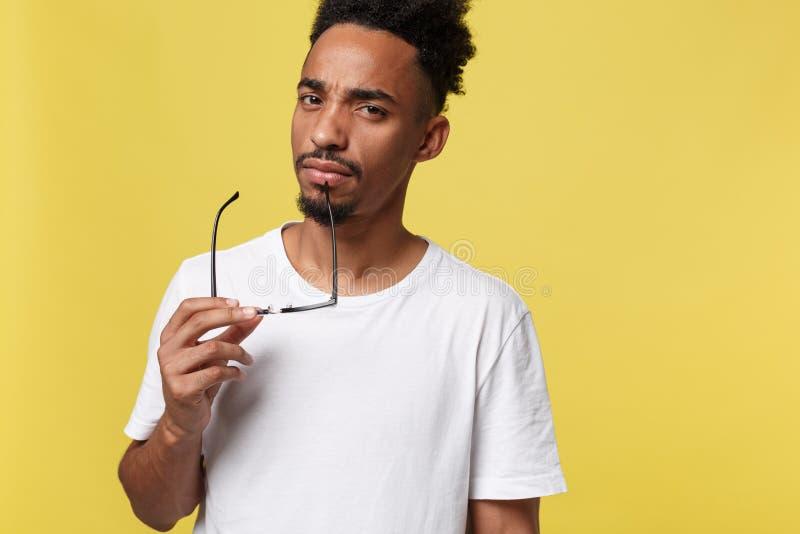Homem de negócio afro-americano que guarda um vidro, isolado no fundo amarelo - pessoas negras imagens de stock