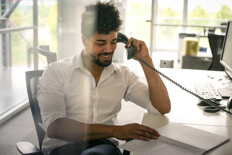 Homem de negócio americano que tem a conversação no telefone da linha terrestre imagem de stock royalty free