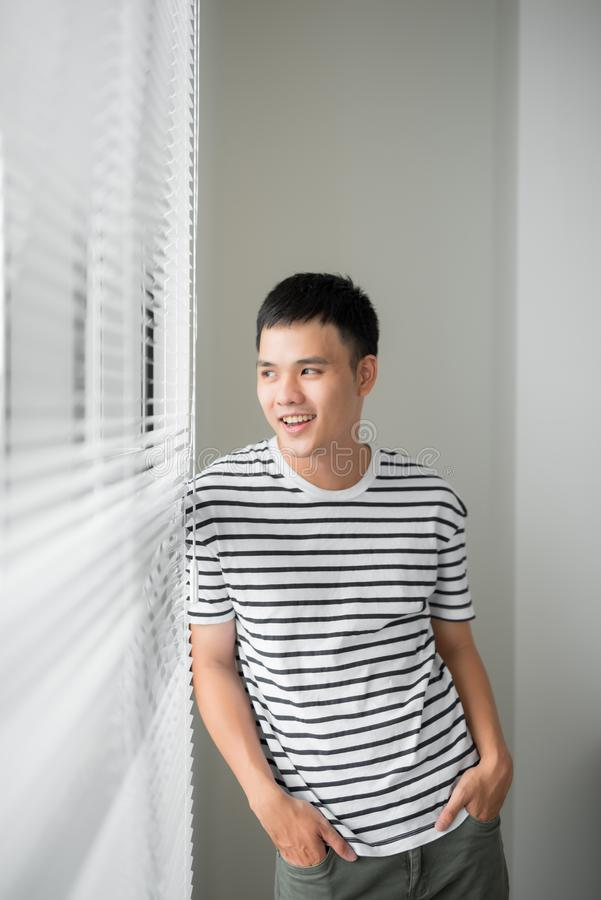Homem de negócio asiático feliz que olha fora de uma janela do escritório fotografia de stock