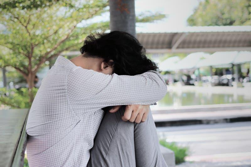 Homem de negócio asiático novo forçado deprimido com as mãos que tocam na cabeça e que sentem desapontados ou esgotadas com traba foto de stock
