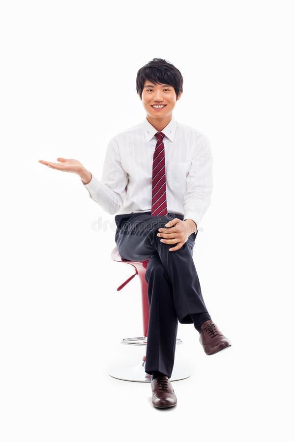 Homem de negócio asiático novo que mostra algo foto de stock royalty free
