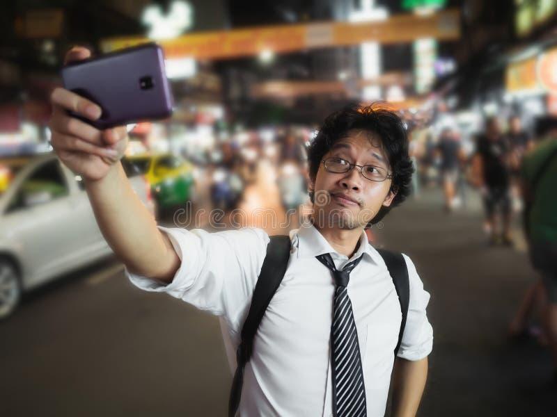 Homem de negócio asiático novo que toma uma imagem ou um selfie na rua na noite Social e Internet do conceito da coisa fotografia de stock royalty free
