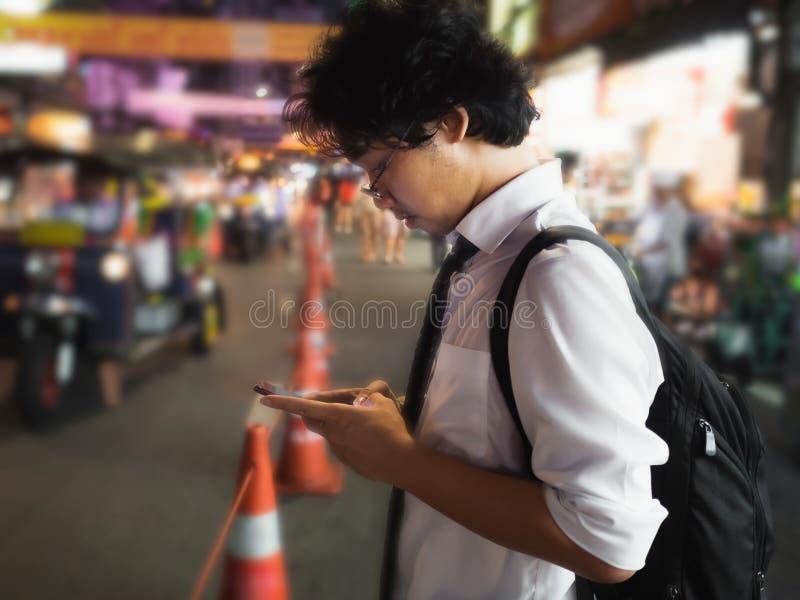 Homem de negócio asiático novo que usa o telefone esperto móvel na rua na noite Social e Internet do conceito da coisa imagens de stock
