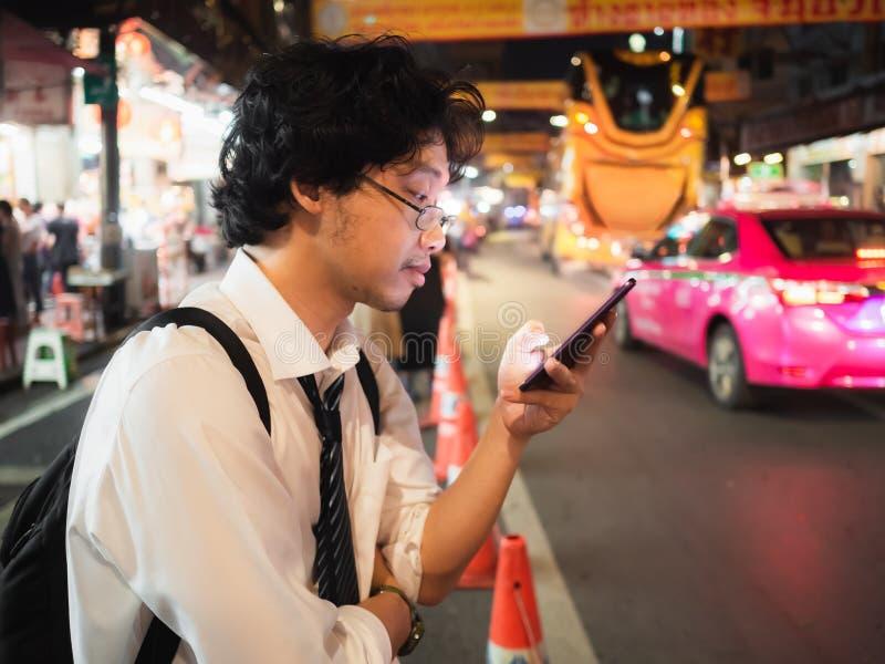 Homem de negócio asiático novo que usa o telefone esperto móvel na rua na noite Social e Internet do conceito da coisa foto de stock royalty free
