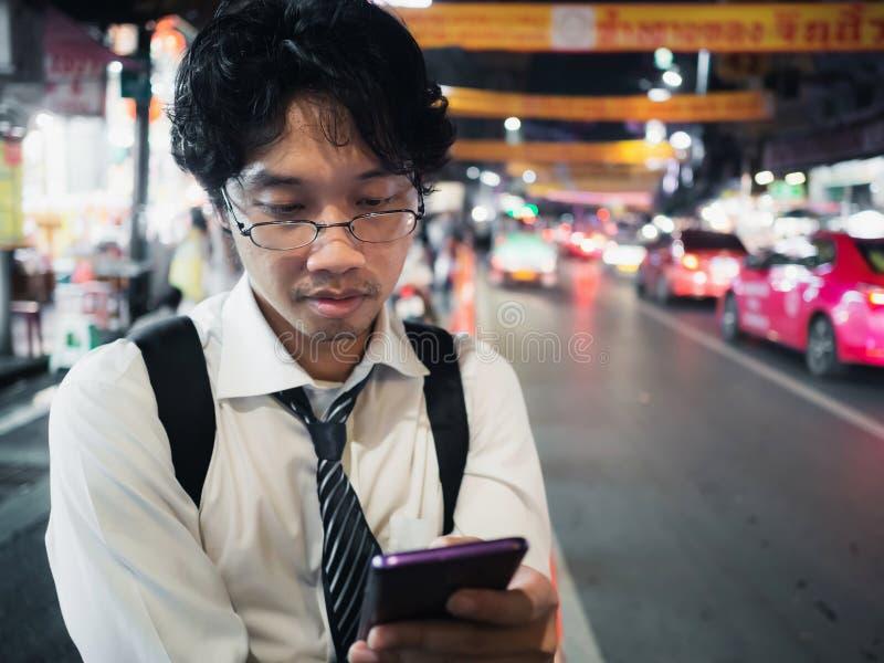 Homem de negócio asiático novo que usa o telefone esperto móvel na rua na noite Social e Internet do conceito da coisa fotos de stock