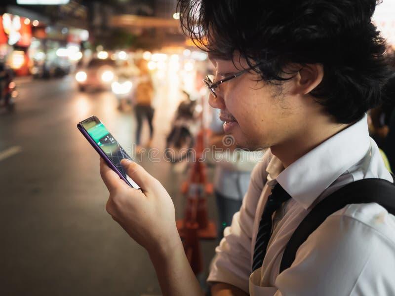 Homem de negócio asiático novo que usa o telefone esperto móvel na rua na noite Social e Internet do conceito da coisa fotos de stock royalty free