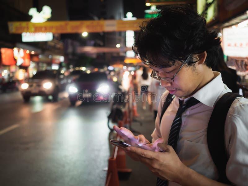 Homem de negócio asiático novo que usa o telefone esperto móvel na rua na noite Social e Internet do conceito da coisa imagem de stock royalty free