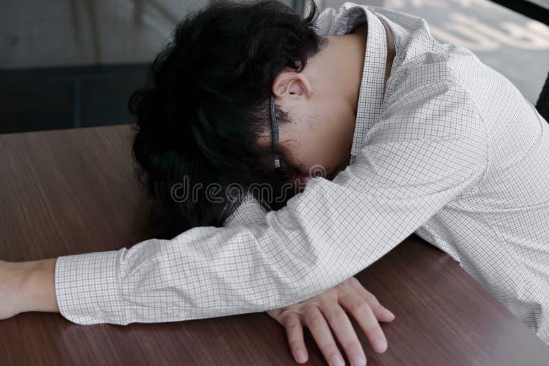 Homem de negócio asiático novo sobrecarregado cansado que encontra-se com cara para baixo na mesa de escritório fotografia de stock