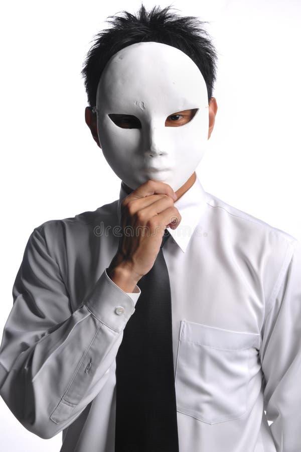 Homem de negócio asiático que esconde atrás da máscara fotografia de stock royalty free