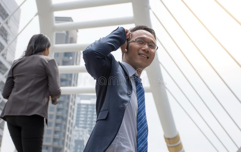 Homem de negócio asiático seguro no terno que olha ausente ao estar fora com telefone celular imagem de stock