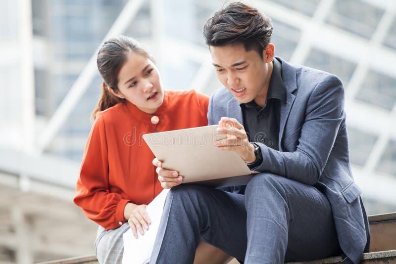 homem de negócio asiático virado das más notícias ou dos problemas na consolação da mulher ou do colega de negócio do portátil ge fotos de stock