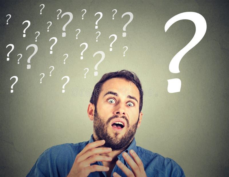 Homem de negócio assustado de vista engraçado surpreendido com muitos pontos de interrogação fotos de stock
