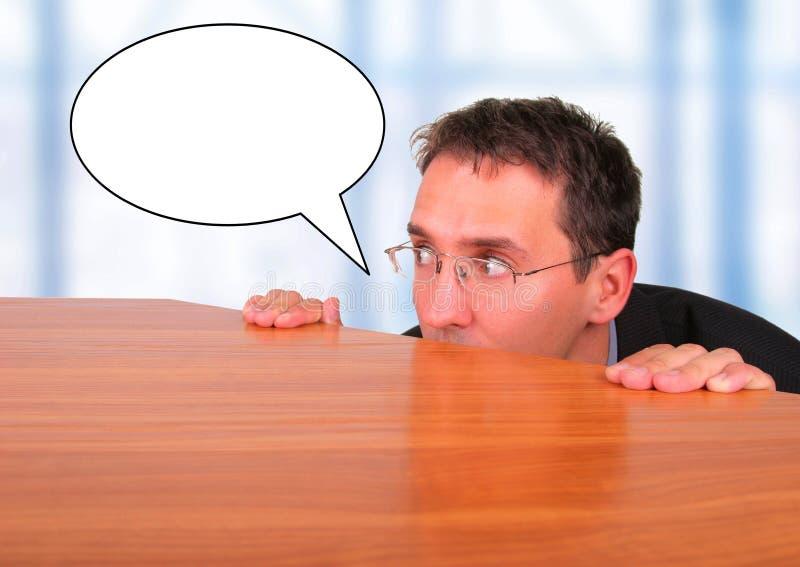 Homem de negócio atrás da mesa no escritório com bolha do discurso imagens de stock