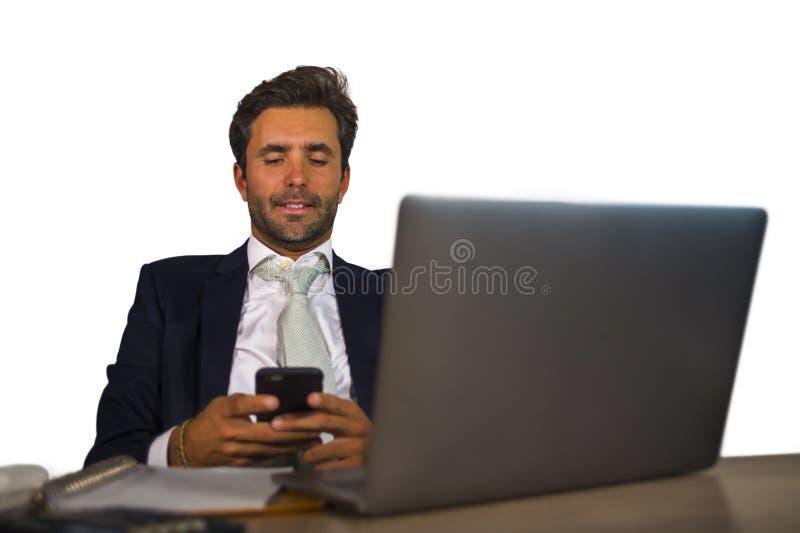 Homem de negócio atrativo e eficiente que trabalha na mesa do laptop do escritório segura no telefone celular de utilização feliz fotografia de stock royalty free