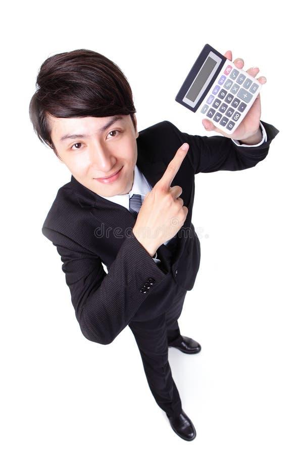 Homem de negócio atrativo que aponta uma calculadora foto de stock