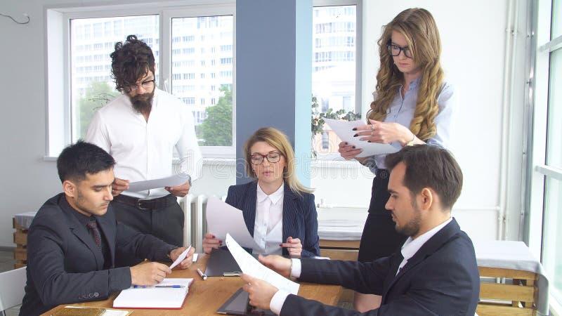 Homem de negócio bem sucedido em uma reunião no escritório Os colegas estão sentando-se na mesa de negócio Conclusão do fotos de stock