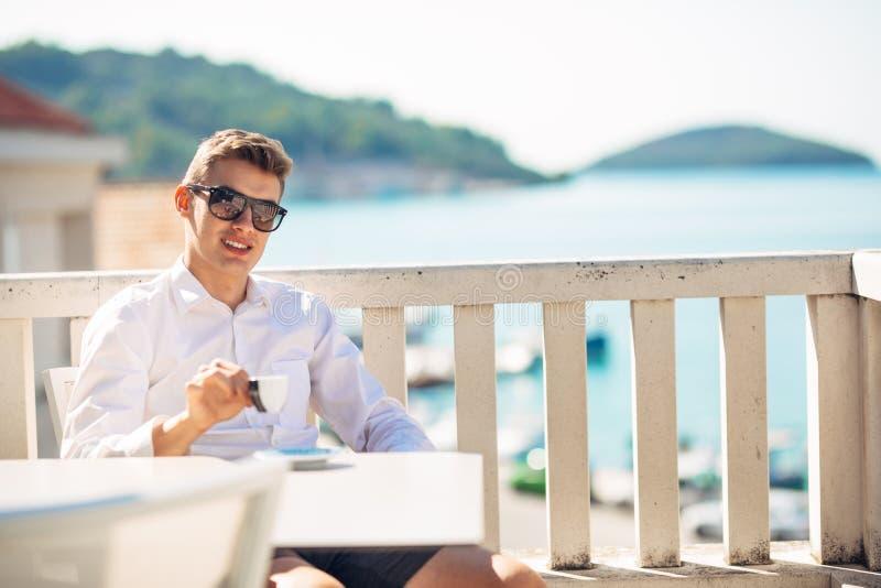 Homem de negócio bem sucedido novo que aprecia a bebida do café do café no café panorâmico marinho ensolarado imagem de stock royalty free