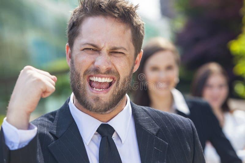 Homem de negócio bem sucedido que comemora com equipe fêmea fotografia de stock