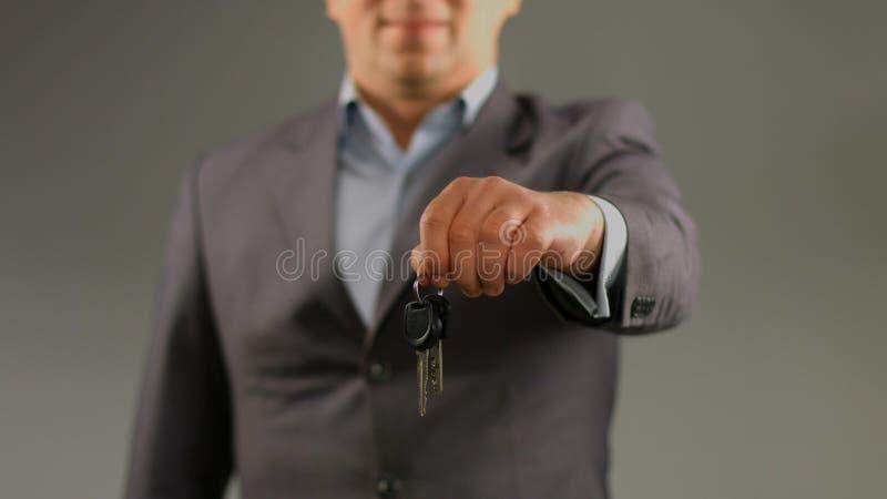 Homem de negócio bem sucedido que guarda a chave, serviço do aluguer de carros, bens imobiliários para a venda fotos de stock royalty free