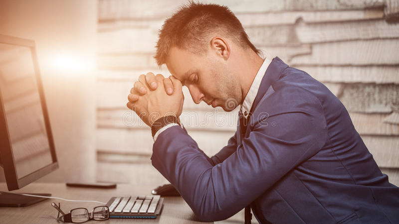 Homem de negócio cansado no local de trabalho no escritório que guarda sua cabeça nas mãos Trabalhador sonolento cedo na manhã ap fotos de stock