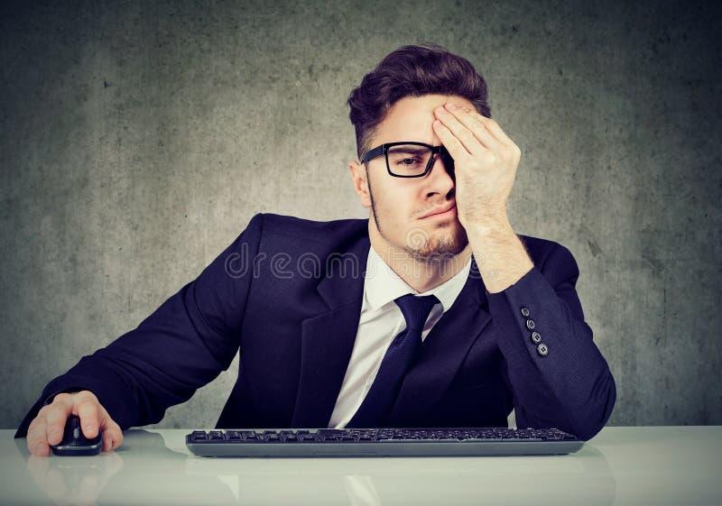 Homem de negócio cansado no local de trabalho fotografia de stock