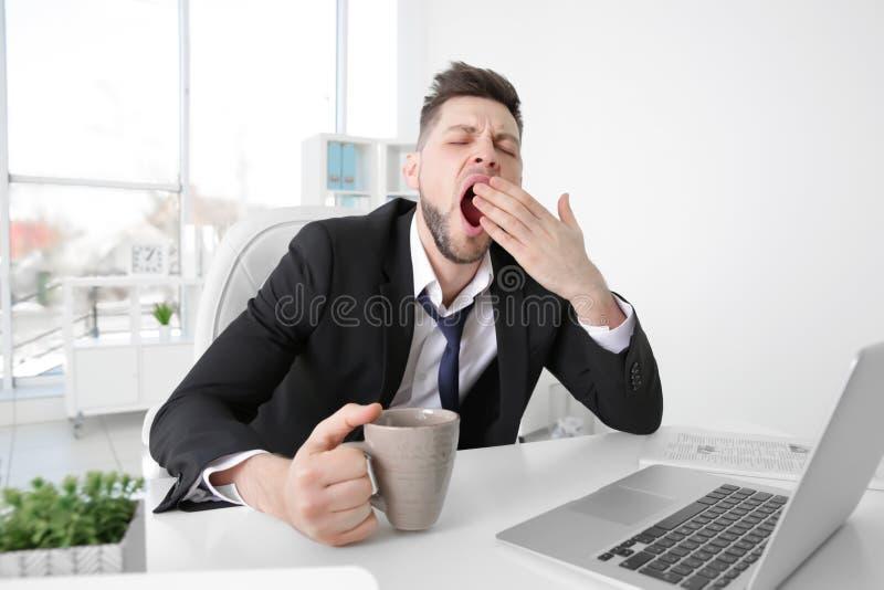 Homem de negócio cansado que boceja no local de trabalho imagens de stock royalty free