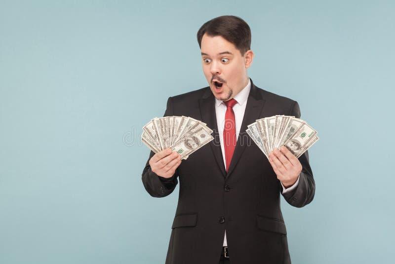 Homem de negócio chocado surpreendido e que guarda muitos dólares imagens de stock royalty free