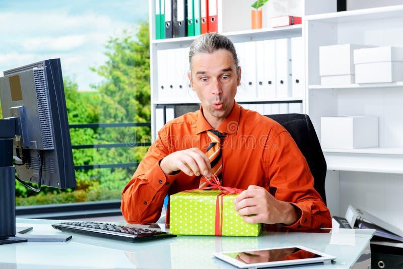 Homem de negócio com a caixa de presente que olha surpreendida imagem de stock