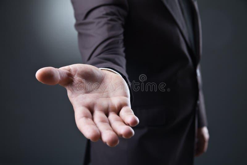 Homem de negócio com mão vazia no fundo escuro foto de stock royalty free