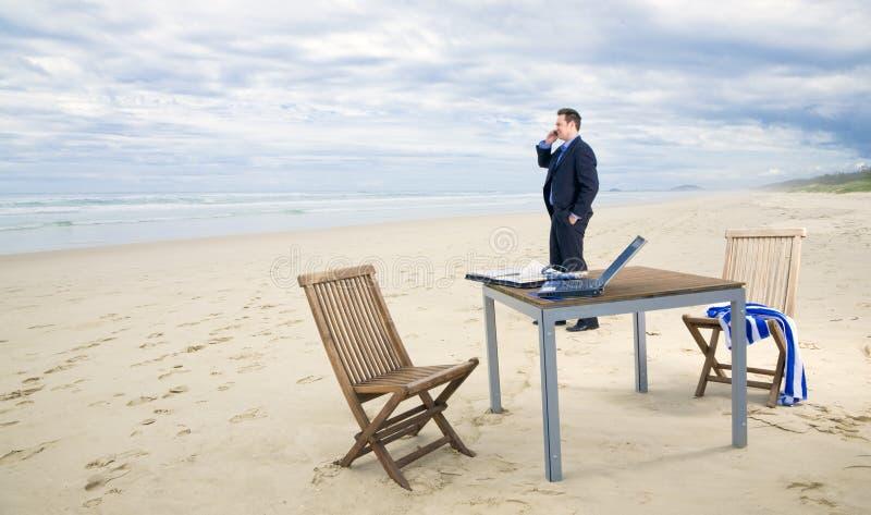 Homem de negócio com o escritório na praia imagens de stock royalty free