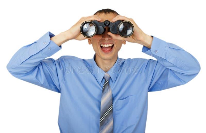 Homem de negócio com o laço azul com binóculos fotos de stock royalty free