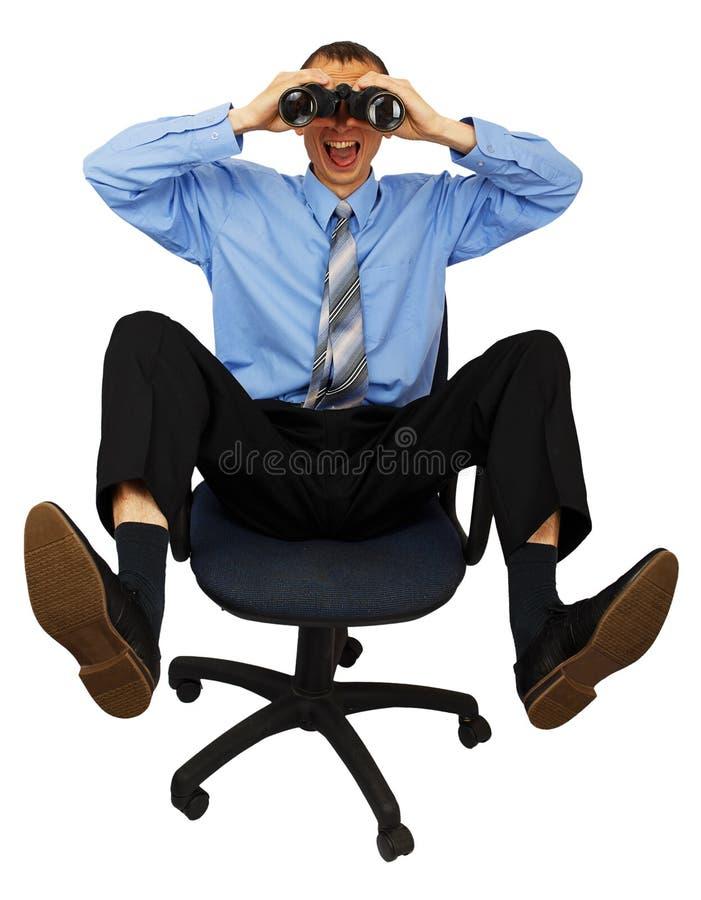 Homem de negócio com o laço azul com os binóculos na cadeira do escritório foto de stock