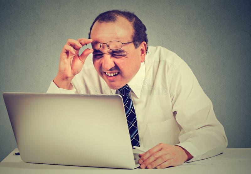 Homem de negócio com os vidros que têm os problemas da visão confundidos com o software do portátil imagens de stock royalty free