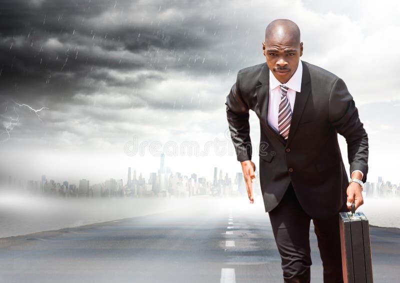 Homem de negócio com a pasta que corre na estrada com skyline e tempestade fotografia de stock
