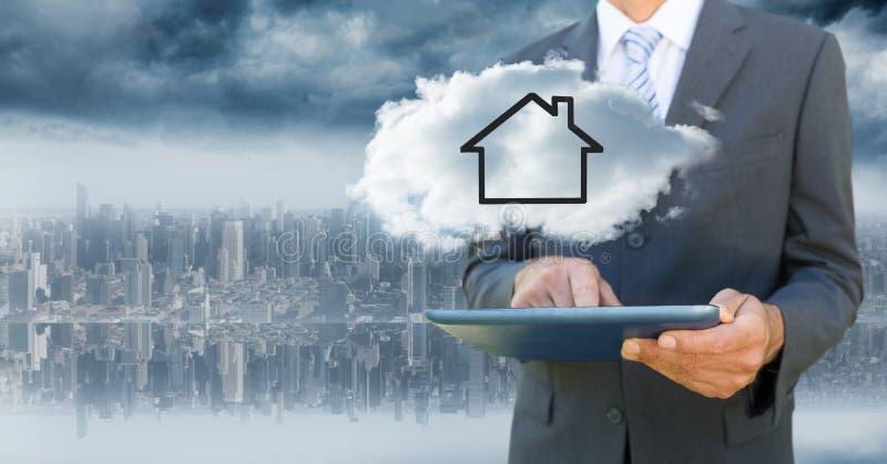 Homem de negócio com tabuleta e nuvem com a casa contra a skyline obscura fotografia de stock
