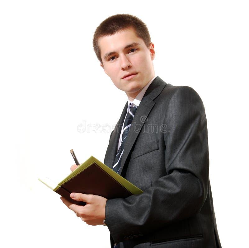 Homem de negócio com um livro e uma pena imagem de stock