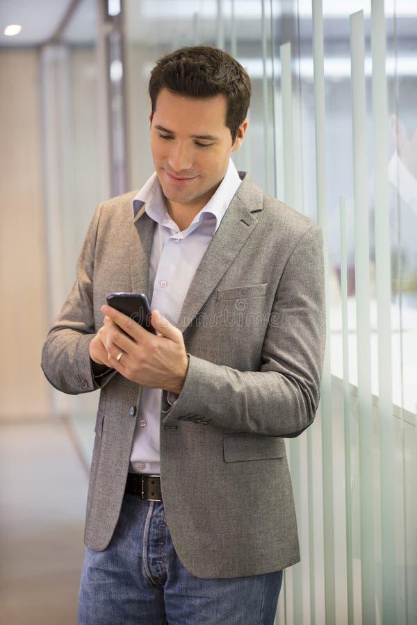Homem de negócio considerável no escritório no telefone, sms, email imagens de stock
