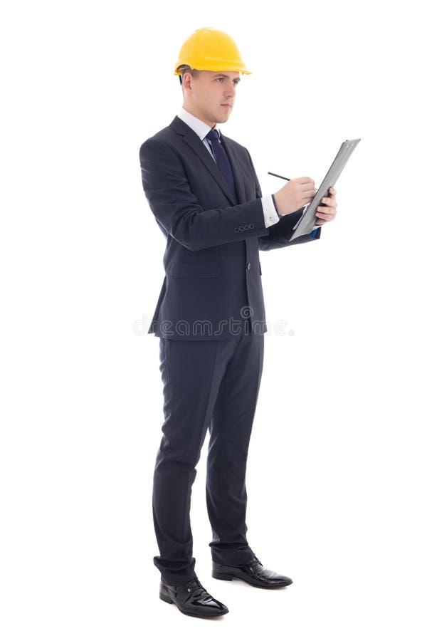 Homem de negócio considerável novo no capacete do construtor amarelo que escreve s imagem de stock royalty free