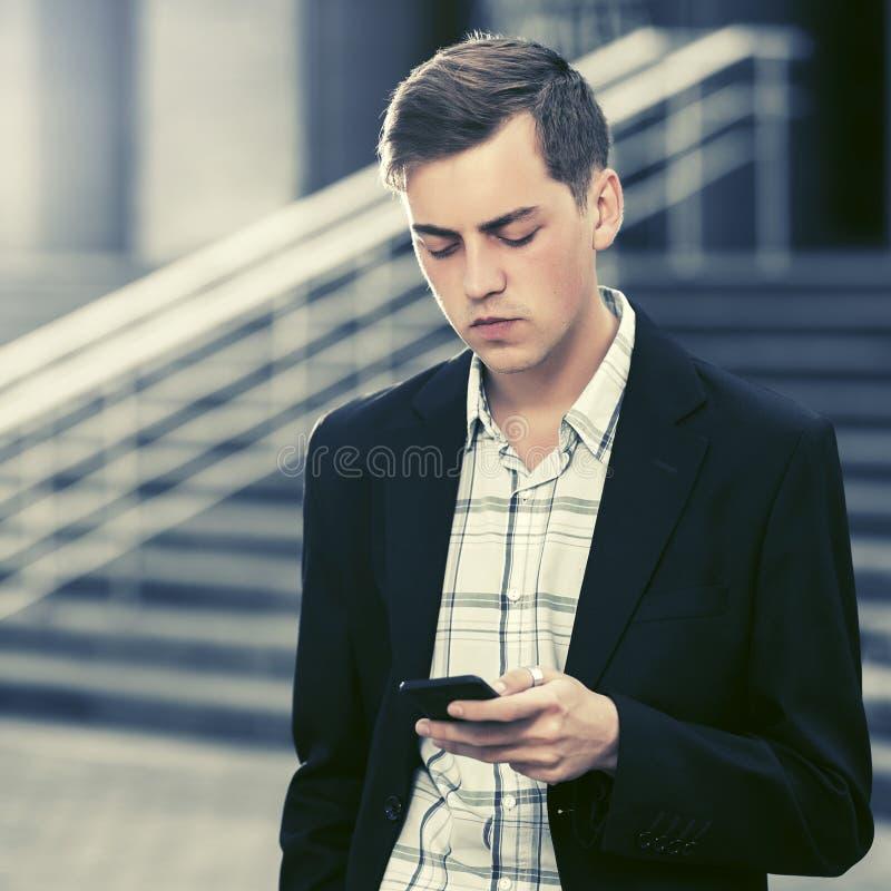 Homem de negócio considerável novo que usa o telefone esperto que anda na rua da cidade fotografia de stock