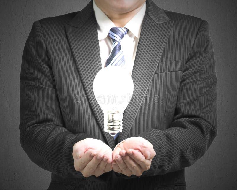 Homem de negócio da abertura da palma com ampola imagens de stock royalty free