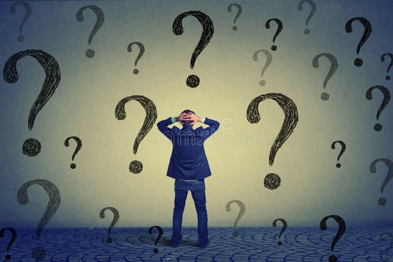 Homem de negócio da vista traseira que está na frente da parede com muitas perguntas imagens de stock