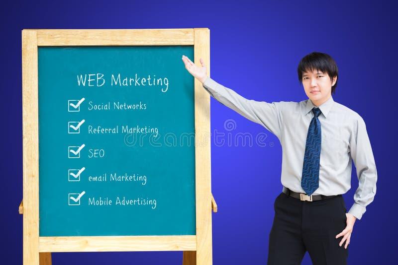 Homem de negócio de Asain que apresenta a planta de mercado do WEB fotos de stock