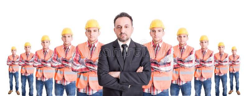 Homem de negócio de Confindent e uma equipe dos trabalhadores da construção fotos de stock royalty free